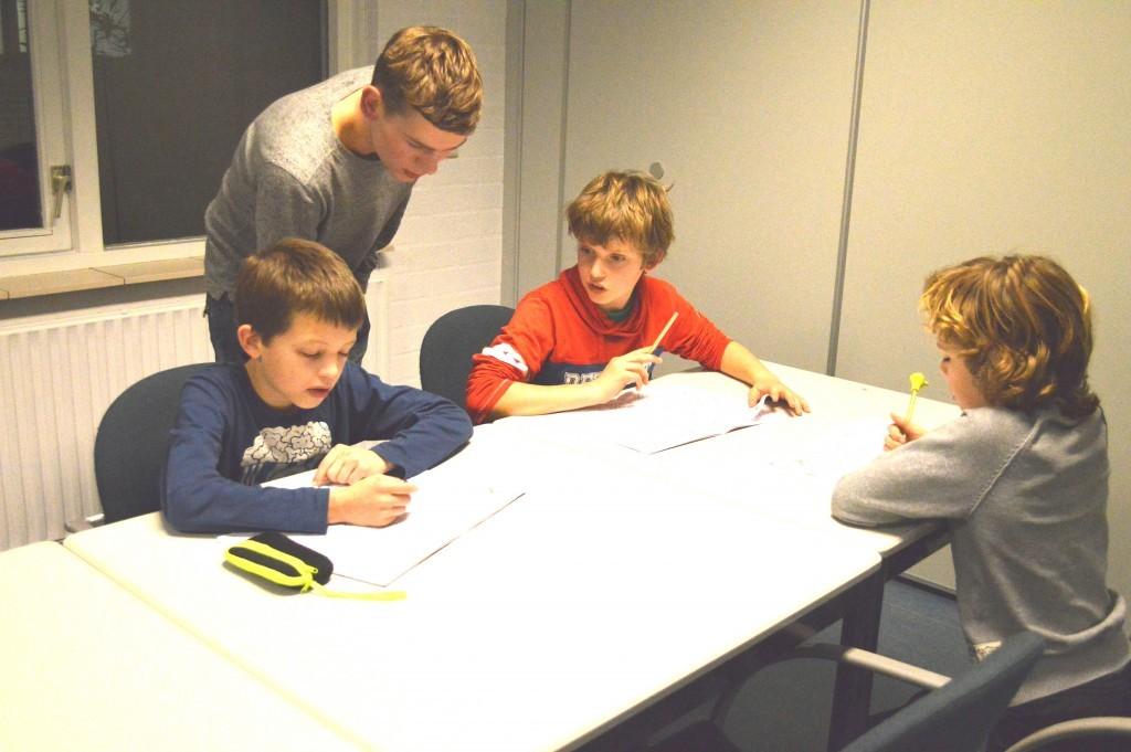 Nick Manshanden helpt de Stap 3-jeugdspelers Yannick, Sem en Lex bij het maken van hun huiswerk.