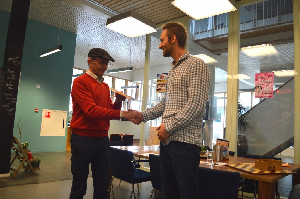 Dirk Beemster overhandigt het eerste exemplaar van 'Vuurtoren, een schaakrelaas' aan Caïssa-Eenhoorn-speler Peter Doggers.