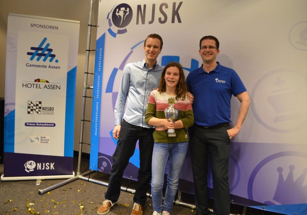 Kersvers Nederlands meisjes B-kampioene Robin Duson wordt geflankeerd door haar trainers Robbert van Dijkhuizen (links) en Jop Delemarre.