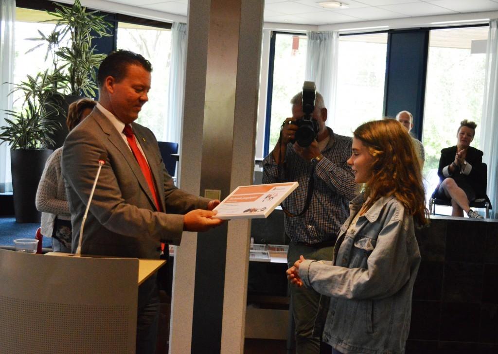 De Hoornse sportwethouder Ben Tap reikt de oorkonde, als blijk van waardering voor haar nationale titel,  aan Robin Duson uit.