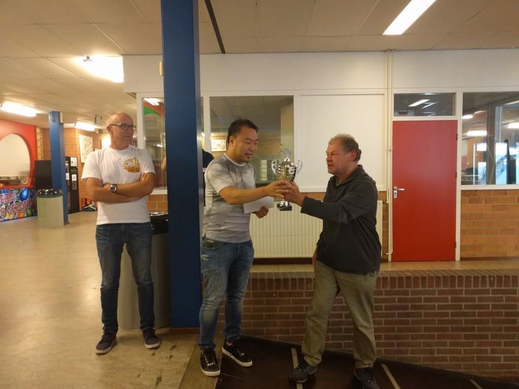 Voorzitter Co Buysman overhandigt de wisselbeker aan de nieuwe Open Hoorns kampioen Yong Hoon de Rover.