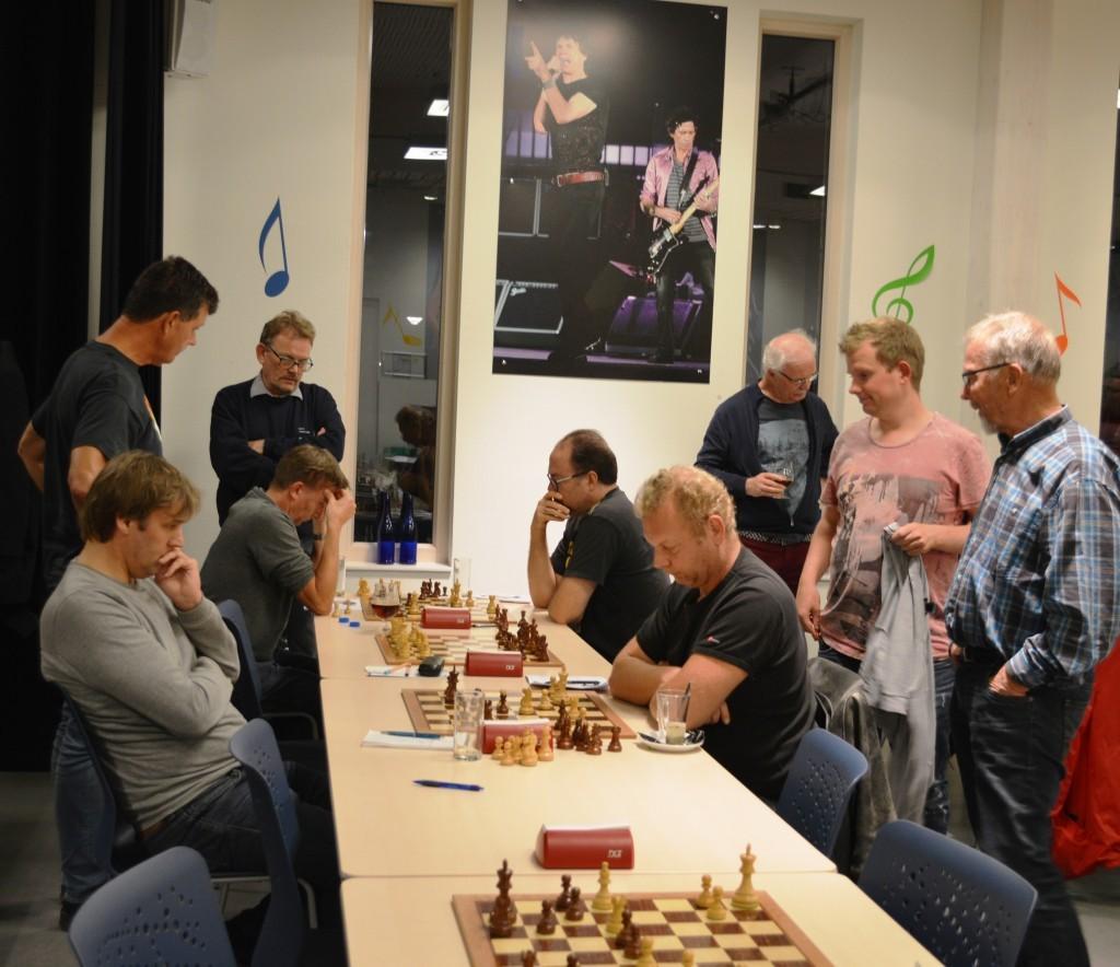 Publieke belangstelling bij de tweede partijen van Caïssa-Eenhoorn 5 - De Groene Zes/Schaaklust 2 die nog aan de hang zijn. Sander Koning (links) zal Eugène Koomen verslaan en kopman Frans Kragten doet hetzelfde tegen Nico Weel, waardoor de eindstand op 5½-½ komt.
